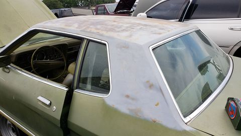 The 1974 Mustang Ghia came with a standard padded vinyl roof, but someone has scraped it off this car.