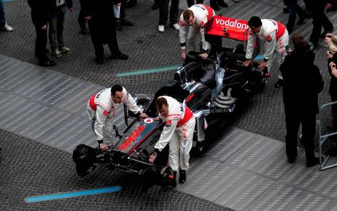 Mechanics roll out the MP4-26 chassis