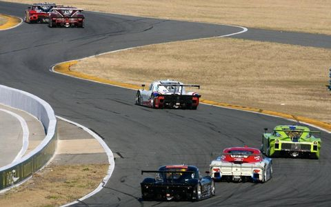 A line of Daytona Prototypes make their way through the Turn 1 complex.