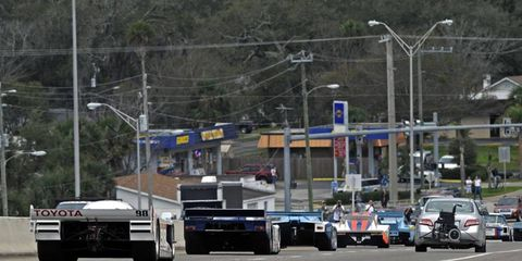 Time warp? Nope, just past winners of the Rolex 24 mixing with Daytona Beach's morning traffic during the Parade of Champions.