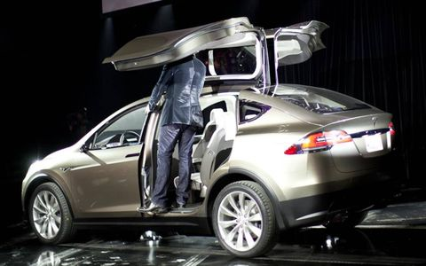 "Elon Musk demonstrates the headroom advantage afforded by the Model X's ""Falcon Wing"" doors"