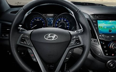 The 2013 Hyundai Veloster turbo includes a leather-wrapped steering wheel and a navigation center.