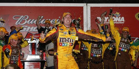 Kyle Busch celebrates after winning the Bud Shootout. He won despite being involved in three crashes.