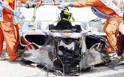 Heikki Kovalainen's shattered McLaren Mercedes is removed by circuit Marshals.