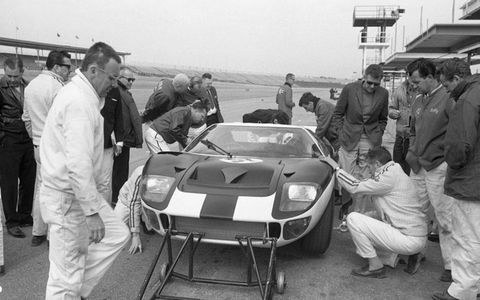 Testing at Daytona. Carroll Shelby is visible to the right of the car. Phil Remington is crouched near the front wheel.
