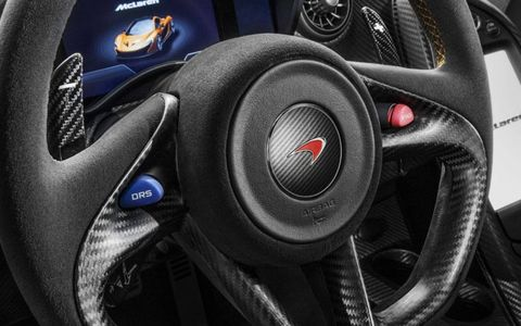 The steering wheel of the McLaren P1 includes buttons for the Drag Reduction System and the hybrid electric powertrain.