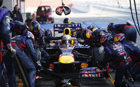 The Red Bull crew works on Sebastian Vettel's RB9 Renault (notice the stop/go board is an Infiniti logo).Photo by: LAT Photographic