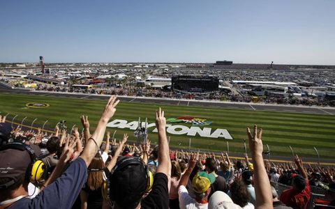 Fans hold up three fingers during the third lap of the race in honor of Dale Earnhardt, who died 10 years in a last-lap crash in the 500.