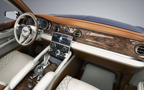 The timber dash panel extends the full width of the cabin, punctuated by a watchlike instrument cluster and traditional eyeball air vents, while the door cappings are trimmed in a deep swath of hand-finished wood.