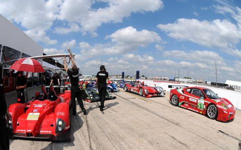 Cars wait in the pit-lane for the start of practice.