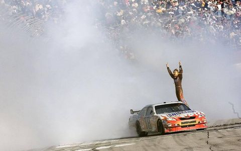 Kyle Busch celebrates his NASCAR Sprint Cup win on the track at Atlanta.