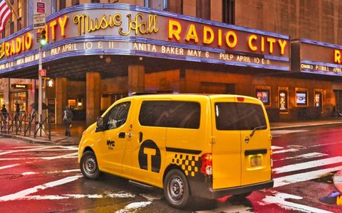 The Nissan NV200 taxi as it drives by Radio City Music Hall in New York City.
