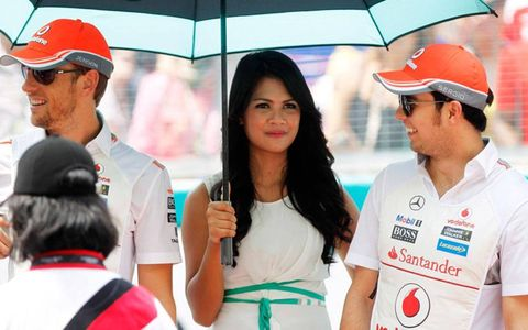 A grid girl in Malaysia does her best to keep the sun off of Formula One driver Sergio Perez, right.