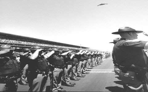 Indiana State Troopers salute and a bomber flies over the front straight before the call for cars to start their engines at the 2005 Indianapolis 500.