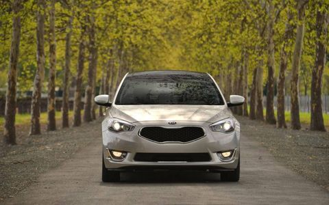 The 2014 Cadenza maintains Kia's tiger nose grille, with LED positioning lights and quad projection beam headlights accented by stretched character lines on the hood.