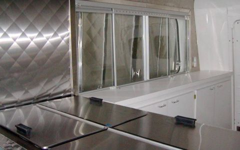 The interior is set up for ice cream vending and comes complete with stainless-steel freezers.