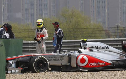 McLaren's Sergio Perez looks at the damage on his MP4-28 race car after running off track during Friday's practice session in Shanghai. Photo by Glen Dunbar/LAT Photographic