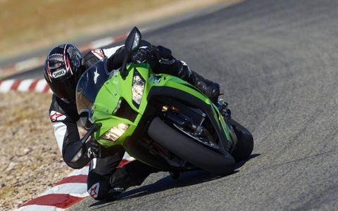 Motorcycle helmet, Helmet, Sports gear, Motorcycle, Sports equipment, Race track, Motorcycle racer, Motorcycling, Personal protective equipment, Motorcycle racing,