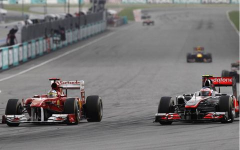 Ferrari's Fernando Alonso makes a move on McLaren's Jenson Button going into turn one during the Malaysian Grand Prix. Photo by: Andrew Ferraro/LAT Photographic
