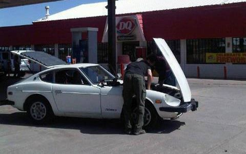 A participant works under the hood of the Datsun after breaking down, again.