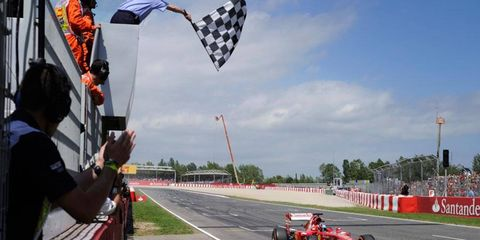 Fernando Alonso takes the checkered flag in Barcelona.
