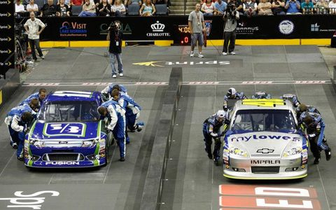 The crews for Matt Kenseth (17) and Jimmie Johnson (48) battle at the NASCAR Sprint Pit Crew Challenge.