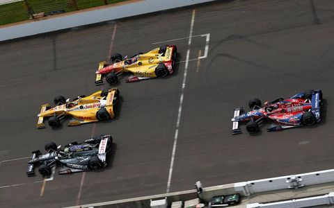 Tony Kanaan takes the low line to make the final pass of Ryan Hunter-Reay for the lead at Indianapolis on Sunday.