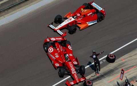 E.J. Viso clips the car of  Dario Franchitti in the pits on lap 15.
