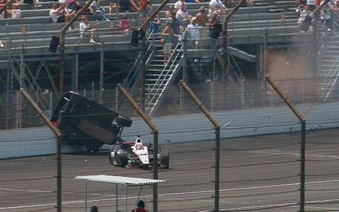 Mike Conway goes high into the fence as the damaged car of series points leader Will Power rolls off course on lap 80.