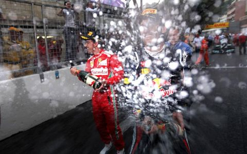 SHOWER TIME//Red Bull Racing's Mark Webber and Fernando Alonso, Ferrari, spray the photographers with Champagne after their first and third-place finishes at the Monaco Grand Prix.