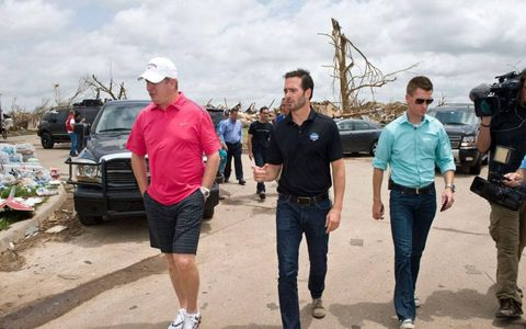 NASCAR driver and five-time champion Jimmie Johnson, center, tours the damage in Moore, Okla., on Thursday.