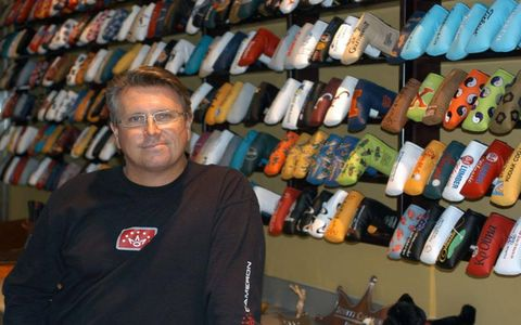 Scotty Cameron in his office with a display of just some of the putter head covers.