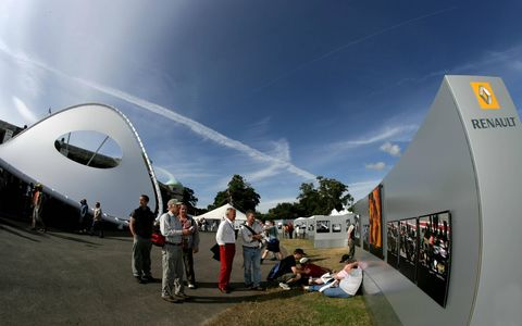 Visitors to the Goodwood Festival of Speed relax near a manufacturer's display.