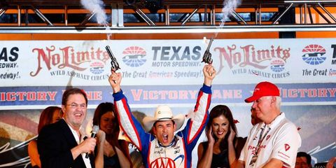 Helio Castroneves celebrates Team Penske's first win of the season with all guns blazing at Texas on Saturday night.