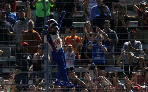 Helio Castroneves lives up to his reputation as the IndyCar Series Spiderman by climbing the fence following his win at Texas.