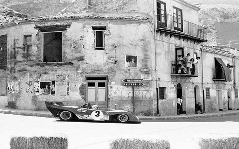 Spectators grab any vantage point they can find to see the winning Ferrari 312PB negotiate the streets of the Italian village of Collesano during the 1972 Targa Florio.