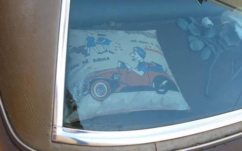 Among the many decorations on the dash and package shelf, this car-themed pillow.