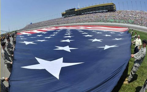 SHOWING THE COLORS//Military personnel help unfurl a gigantic American flag prior to the NASCAR race at Kansas Motor Speedway.
