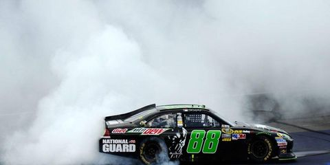 Dale Earnhardt Jr. begins the celebration of a win with a burnout in front of the main grandstands and Michigan International Speedway.