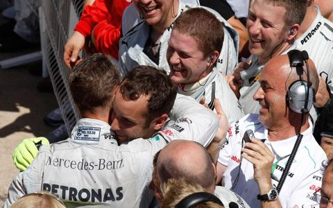 Michael Schumacher, left, celebrates his first podium of the season with his crew after a third-place finish at Valencia.