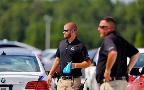 Instructors at the BMW Performance driving school look on they prepare vehicles for the next segment of challenges.
