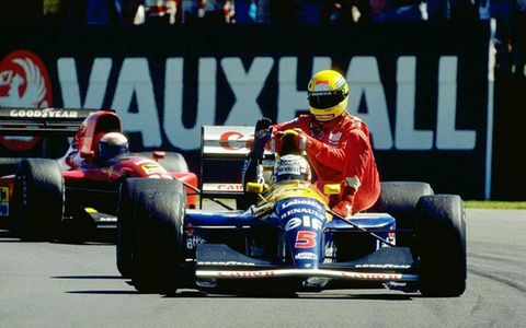 Ayrton Senna gets a ride back to the pits on the sidepod of Nigel Mansell's car.