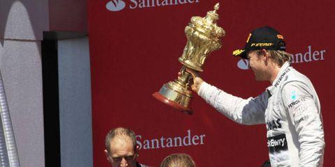 Nico Rosberg hoist trophy after winning at Silverstone.