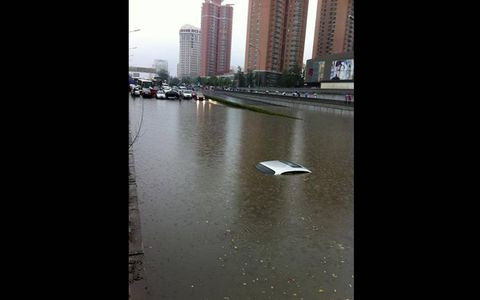 No-Drive Zone//A car is submerged in Beijing after rainstorms pounded the Chinese capital recently. The storms delayed flights, slowed road traffic and disrupted the operation of subway lines in the afternoon rush hours.