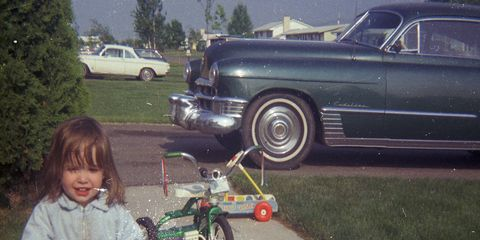 Summer of 1969: My little sister with my tricycle, her Creative Coaster, my mom's '49 Cadillac coupe and the neighbors' Corvair.