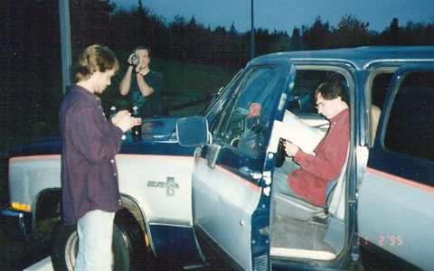 Anyone up for a game of Spot the Anachronisms? Giant shirts! Hi8 camcorder! Road atlas! (Not shown: rest stop pay phone, which is likely why we've stopped.) The author helms the Suburban, 1995.