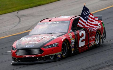Brad Keselowski raises the flag after giving Ford its fourth consecutive win in the NASCAR Sprint Cup Series.