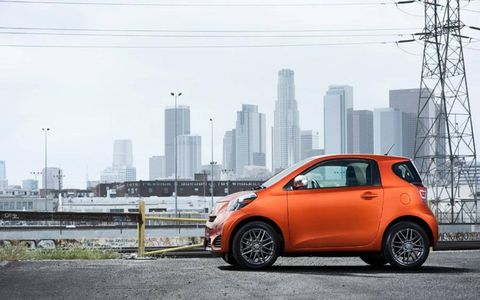 A side shot of the 2012 Scion iQ in front of the cityscape