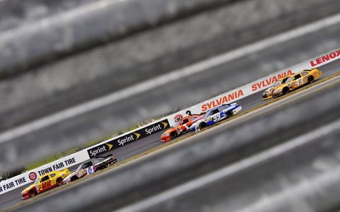 Sam Hornish Jr., subbing for suspended Penske Racing driver A.J. Allmendinger, duels with defending Sprint Cup Series champion Tony Stewart at New Hampshire Motor Speedway. In the end, Kasey Kahne won the race, with Stewart 12th and Hornish 22nd.