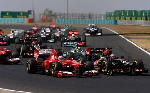 Fernando Alonso, left, and Romain Grosjean, right, battle for position at the start of the Hungarian Grand Prix.